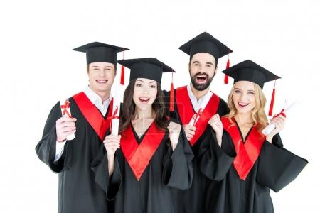 Foto de Happy young students in academic caps holding diplomas and smiling at camera  isolated on white - Imagen libre de derechos