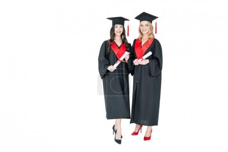 Photo pour Two beautiful young students in academic caps holding diplomas and smiling at camera   isolated on white - image libre de droit