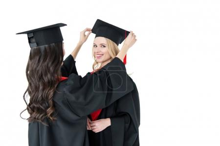 Foto de Two young happy women in mortarboards standing together  isolated on white - Imagen libre de derechos