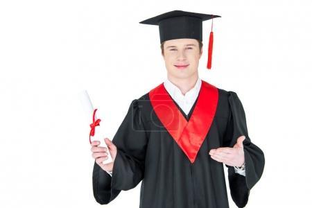Photo pour Jeune homme souriant en chapeau de fin d'études détenant un diplôme isolé sur blanc - image libre de droit