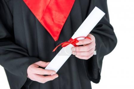 Photo pour Vue rapprochée partielle du jeune homme en robe de fin d'études titulaire d'un diplôme isolé sur blanc - image libre de droit
