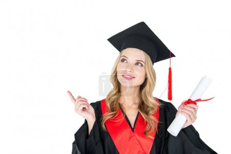 Photo for Beautiful young blonde woman in mortarboard holding diploma pointing away with finger isolated on white - Royalty Free Image