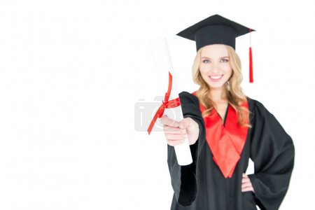 Photo for Close-up view of smiling student in graduation gown holding diploma isolated on white - Royalty Free Image