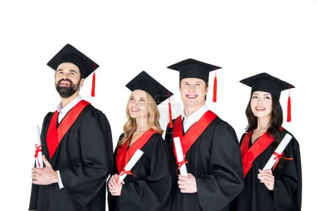 Photo pour Happy students in graduation gowns and mortarboards holding diplomas  isolated on white - image libre de droit