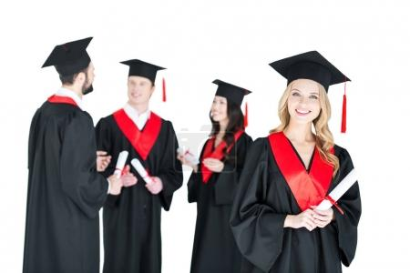 Photo pour Happy young woman in mortarboard holding diploma and friends standing behind  isolated on white - image libre de droit