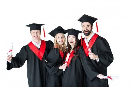 Photo pour Happy young men and women in academic caps holding certificates and smiling isolated on white - image libre de droit