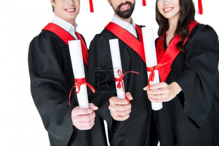 Foto de Cropped shot of smiling students in graduation gowns holding diplomas  isolated on white - Imagen libre de derechos