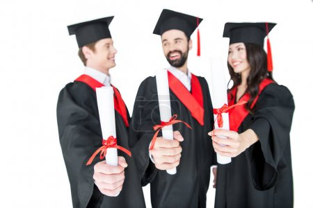 Foto de Happy students in graduation caps holding diplomas and smiling each other isolated on white - Imagen libre de derechos