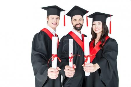 Foto de Happy students in graduation caps holding diplomas and smiling at camera  isolated on white - Imagen libre de derechos
