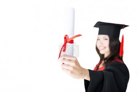 Photo pour Vue rapprochée d'un étudiant souriant en robe de remise des diplômes portant un diplôme isolé sur blanc - image libre de droit
