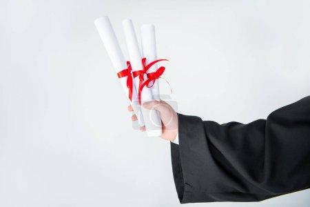 Photo pour Vue rapprochée partielle des étudiants titulaires de diplômes isolés en gris - image libre de droit