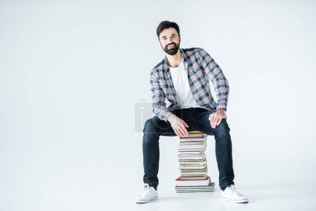 student sitting on pile of books