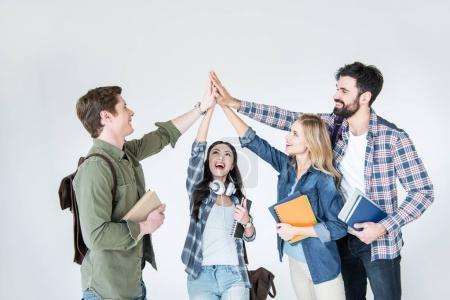 Photo pour Quatre jeunes étudiants en vêtements décontractés tenant des livres et donnant highfive isolé sur blanc - image libre de droit