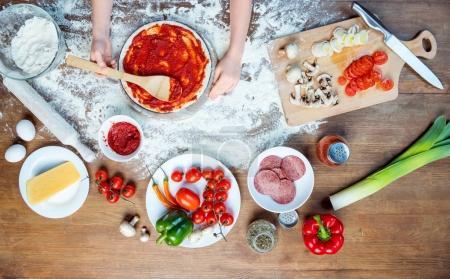 Photo pour Vue de dessus d'enfant faisant pizza avec des ingrédients de pizza, tomates, salami et champignons sur le dessus de table en bois - image libre de droit
