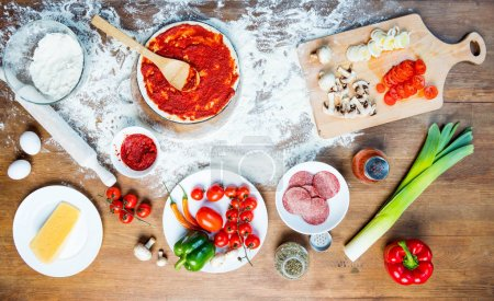 Photo for Top view of pizza ingredients, tomatoes, salami and mushrooms on wooden tabletop - Royalty Free Image
