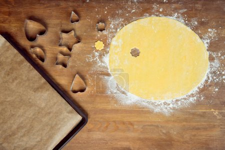 Photo for Top view of raw shaped cookie, dough and and cookie cutters on wooden table - Royalty Free Image
