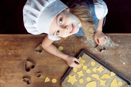 Photo for Top view of girl with raw shaped cookies on baking tray and cookie cutters on wooden table - Royalty Free Image