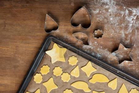 Photo for Top view of raw shaped cookies on baking tray and cookie cutters on wooden table - Royalty Free Image
