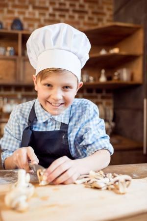 boy cutting mushrooms