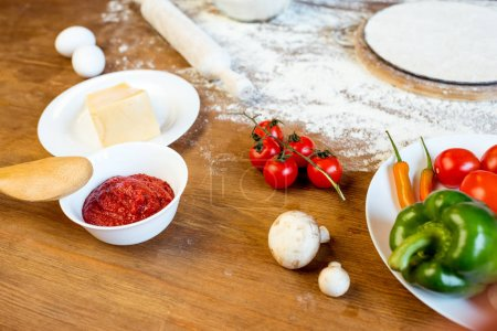 Photo for Different pizza ingredients, vegetables and dough on wooden tabletop - Royalty Free Image