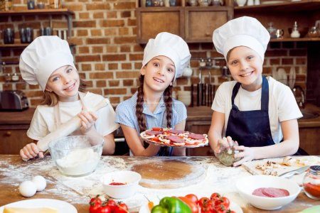 Photo for Kids in chef hats making pizza together - Royalty Free Image