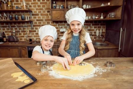 Photo for Little kids in chef hats making shaped cookies in kitchen - Royalty Free Image