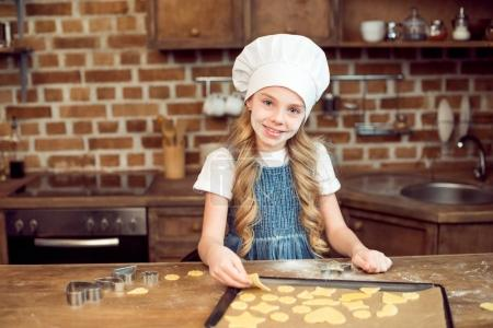 Photo for Portrait of little girl in chef hat making shaped cookies in kitchen - Royalty Free Image