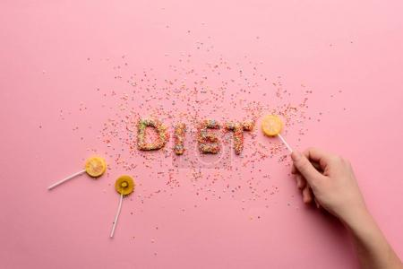 Photo for Top view of word diet made from candies and hand holding lollipop, healthy eating concept - Royalty Free Image