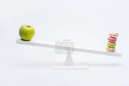 Apple and macarons on seesaw