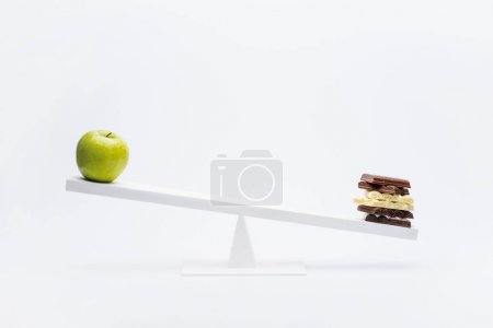 Photo for Close-up view of apple and chocolate balancing on seesaw, healthy living concept - Royalty Free Image