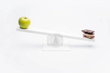 Apple and chocolate on seesaw