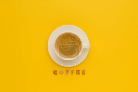 Photo for Top view of cup of fresh hot coffee and word coffee isolated on yellow - Royalty Free Image