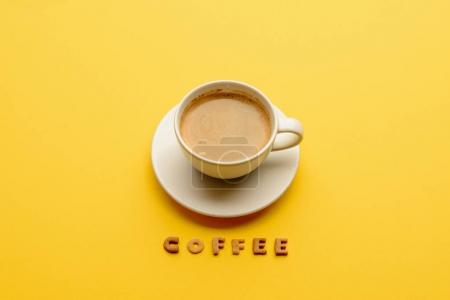 Photo for Close-up view of cup of fresh hot coffee and word coffee isolated on yellow - Royalty Free Image