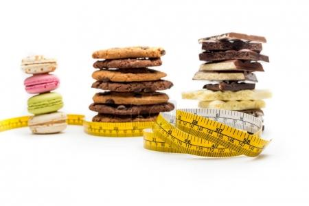 Photo for Macaroons, cookies, chocolate bars and measuring tape isolated on white - Royalty Free Image