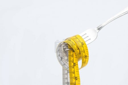 Photo for Measuring tape on fork isolated on white, healthy living concept - Royalty Free Image
