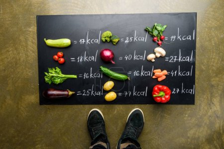 Photo for Partial view of man standing near fresh vegetables and calories table, healthy lifestyle concept - Royalty Free Image