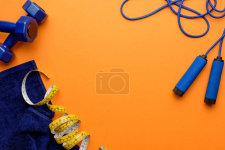 Photo for Various sports equipment, measuring tape and towel isolated on orange - Royalty Free Image