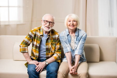 Photo for Happy senior couple sitting together on sofa and smiling at camera - Royalty Free Image