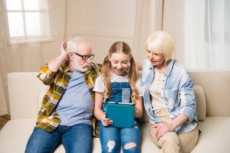 Grandparents and child with digital tablet
