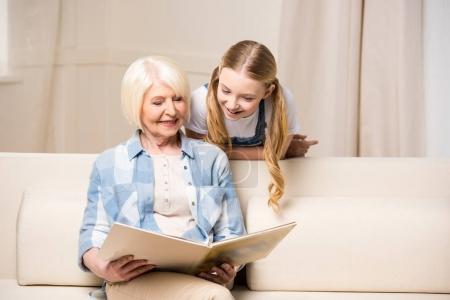 Photo pour Bonne grand-mère et petite-fille regardant l'album photo à la maison - image libre de droit