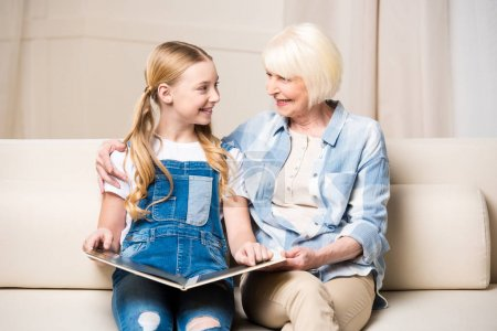 Grandmother and girl with photo album