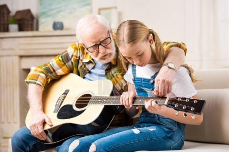 Grandfather and granddaughter with guitar