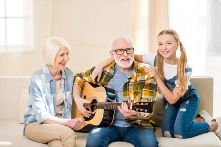 Photo for Cute happy girl with grandparents sitting together on sofa and playing acoustic guitar - Royalty Free Image
