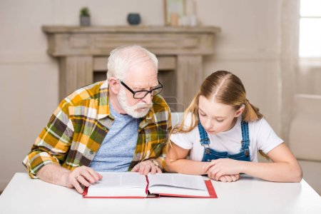 Grandfather with girl reading book
