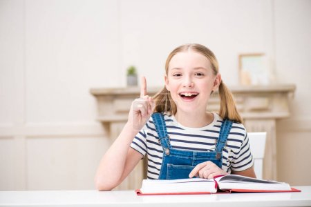 Photo for Adorable smiling girl reading book and pointing up with finger - Royalty Free Image