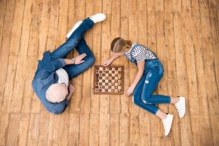 Photo for Top view of grandfather and granddaughter playing chess on hardwood floor - Royalty Free Image