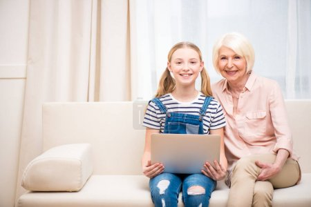 Girl with grandmother using laptop
