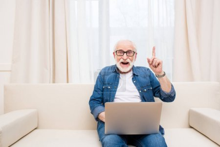 Photo for Smiling senior man using laptop and pointing up with finger - Royalty Free Image