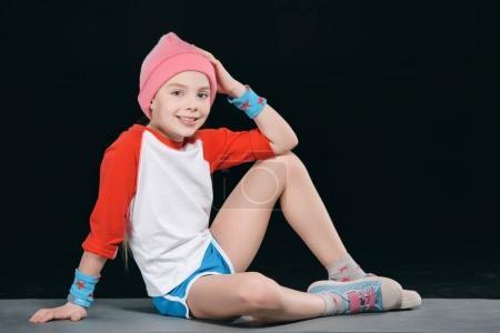 girl in sportswear sitting on mat