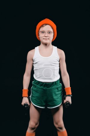 Photo for Boy training with dumbbells isolated on black. athletics children concept - Royalty Free Image